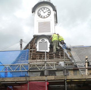 Tiles are removed from the roof around the clock tower.
